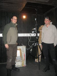 two people standing next to light dome sensor