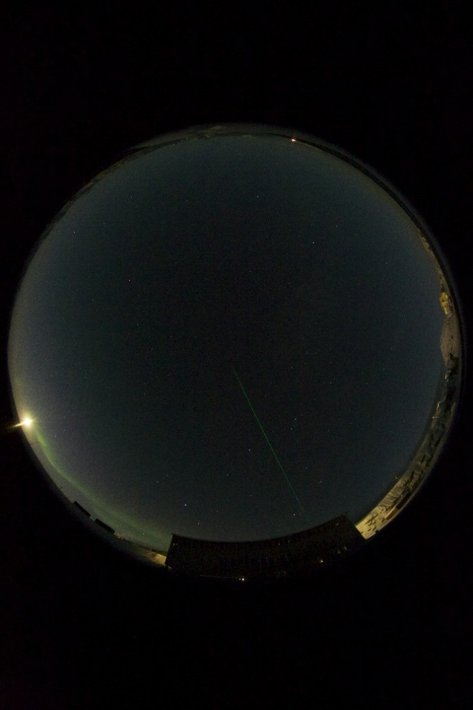 All sky image of the sky in Ny-Ålesund together with the marinelab and the laser beam from the Alfred Wegner Institute observatory (photo: Geir Johnsen)