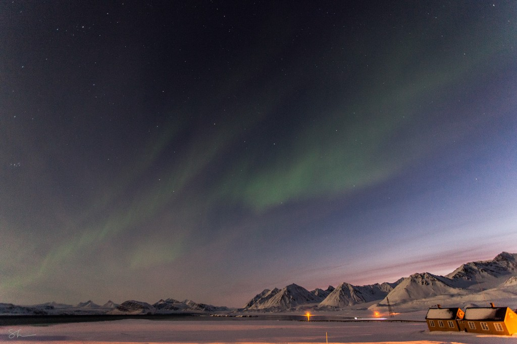 The Aurora Borealis serve as a light source in the skies over Ny Alesund.